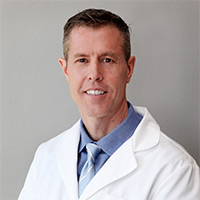 Image of Brian Loveridge in white lab coat, blue shirt, and blue tie.
