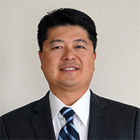 Image of Dr. David Hall in black suit jacket white shirt, and black and blue striped tie.